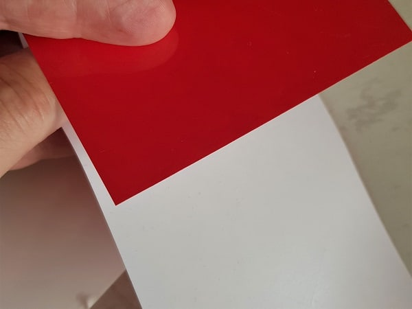 Red heat transfer vinyl showing the shiny side that needs to go against the cutting mat.