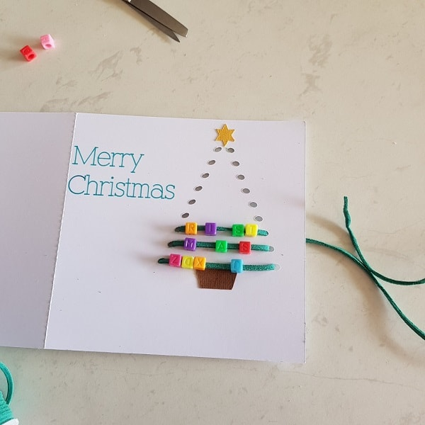 Threaded Christmas Tree card being threaded with the beads being added on each line of threading.