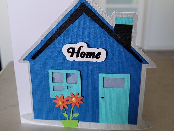 Finished shaped house card with the home sign on the front and the flowers embellishing the frontage.